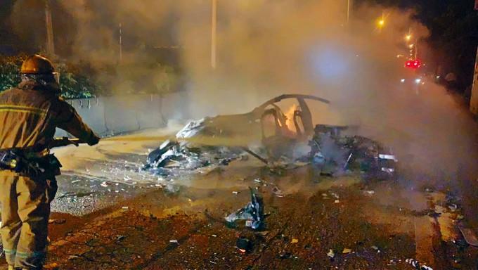 一輛特斯拉在撞車後燃燒,消防到場滅火。