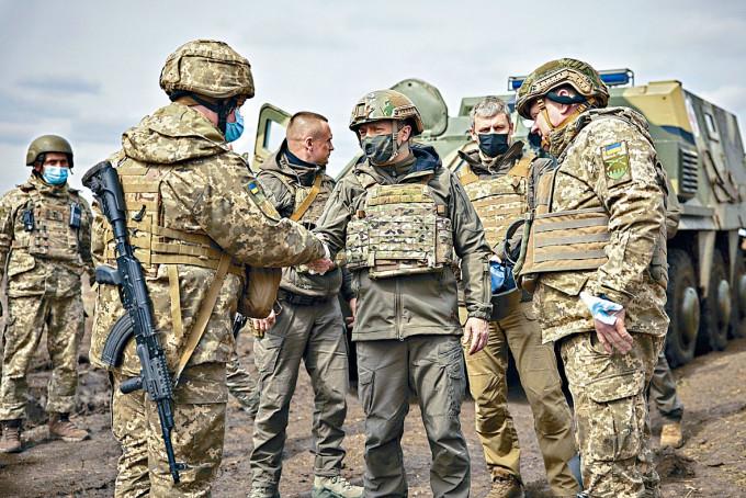 烏克蘭總統澤連斯基(中)周四到東部前綫視察,與士兵握手。