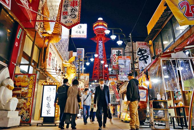 大阪地標「通天閣」前戴口罩的行人。