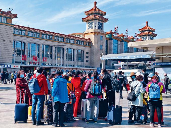北京火車站前昨日有大批拎着行李的旅客。