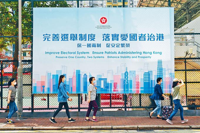 市民在旺角街頭步過完善選舉制度,落實愛國者治港廣告牌。