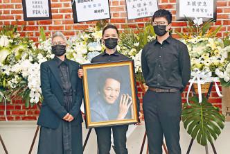 敏兒偕兩子讓傳媒拍照,智叔的遺照由長子文哲捧着。