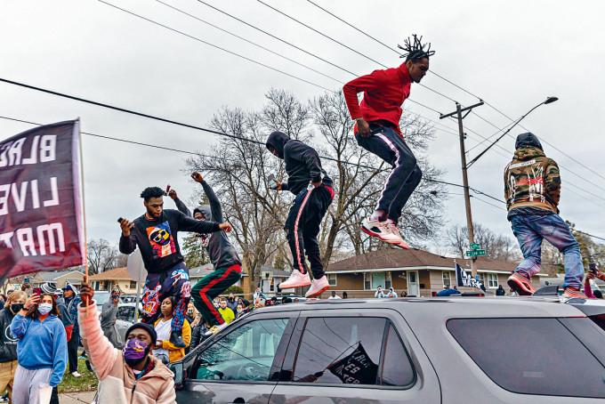 在明尼阿波利斯,示威者周日站在警車頂抗議。