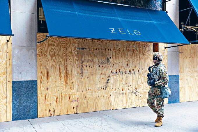 明尼阿波利斯市國民警衞軍在一間封上木板的店鋪外巡邏。