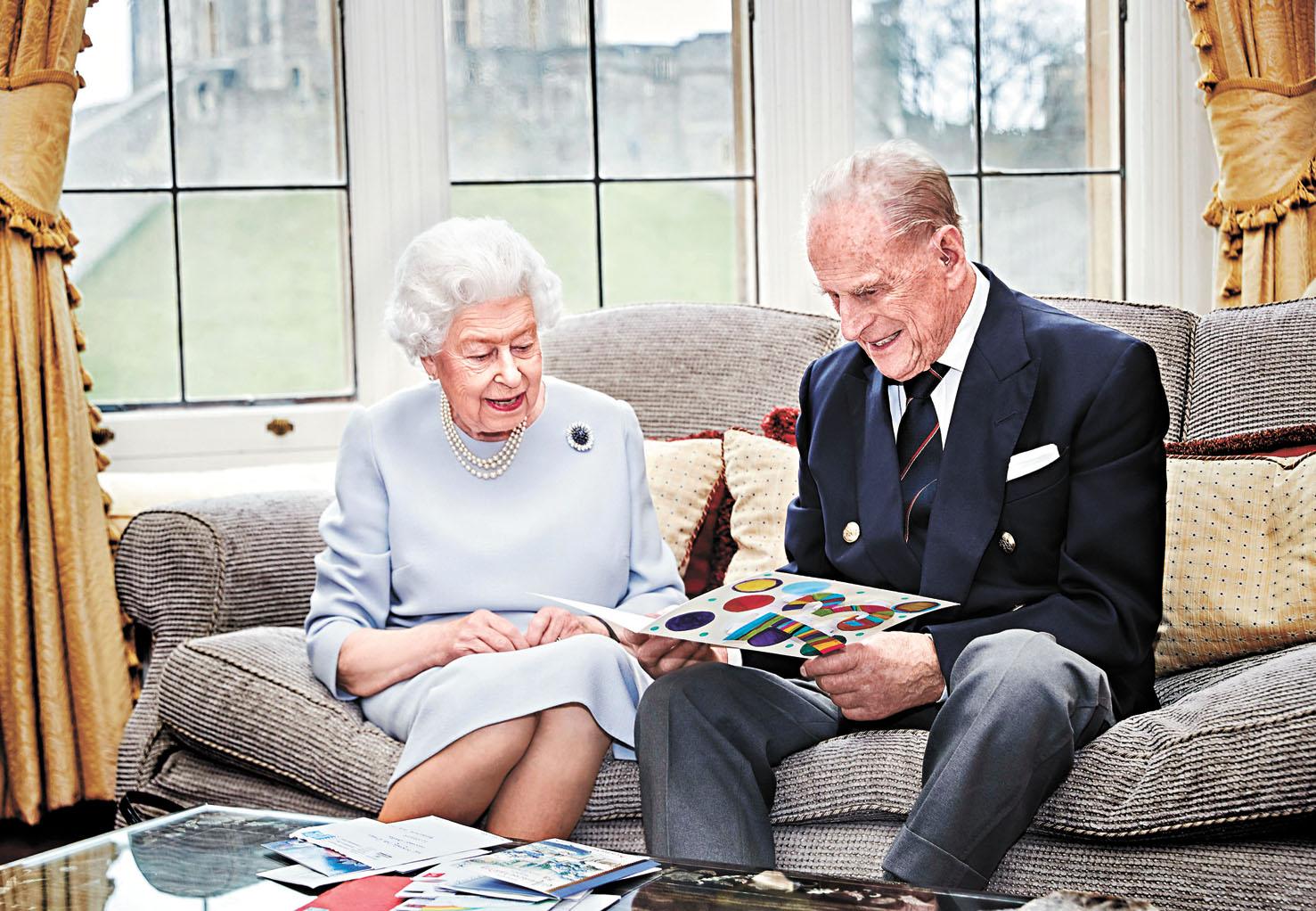 菲臘親王陪英女王走過73載的風雨,圖為兩人去年坐在一起看自製的結婚紀念卡。美聯社資料圖片