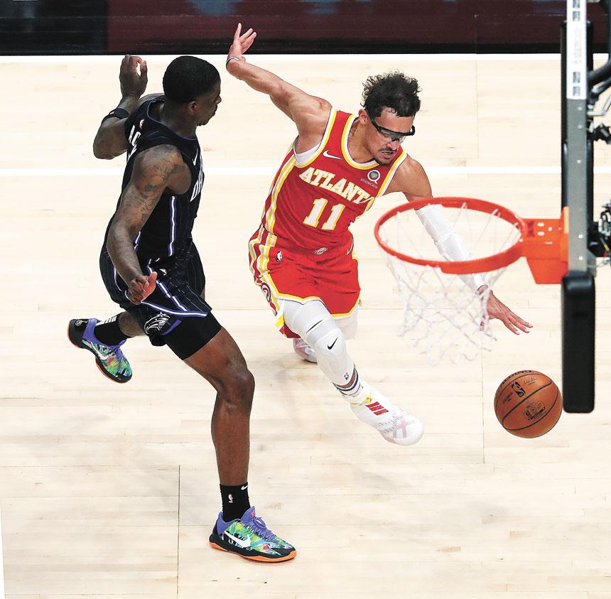 常規賽對陣魔術,老鷹隊球員特雷.楊(右)擺脫防守運球到籃下。美聯社