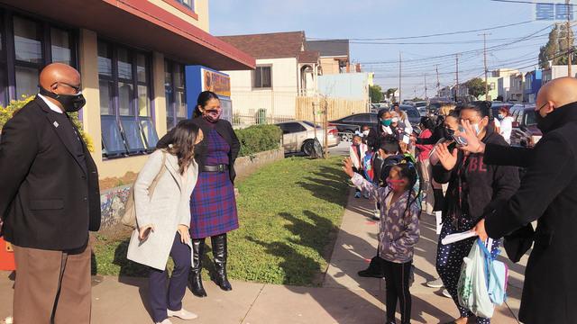 (左起)三藩市校區學監馬菲斯、華裔教委林謙悅和市長布里德在灣景區Bret Harte校門外迎接第一批重回學校的小學生們。記者徐明月攝