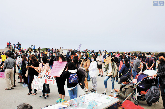 許多居民手舉自製標示牌聲援亞裔社區。記者張曼琳攝