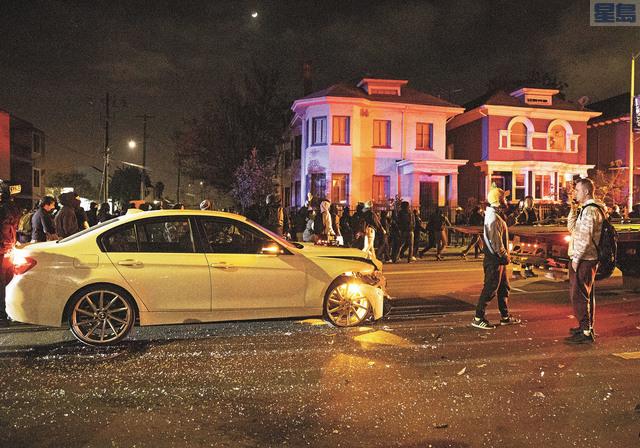 示威者遊行經過一個撞車現場。 美聯社