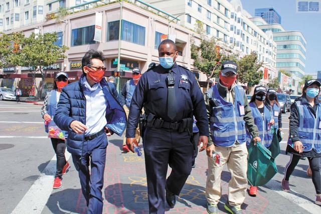 穆倫斯警官(中)、屋崙華埠商會會長陳錫澎(左)和華埠義工巡邏隊的成員們一起巡街並向商戶發放汽笛。記者張曼琳攝