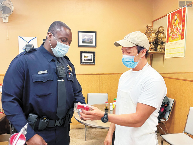 穆倫斯警官(左)向在華埠餐廳工作人員介紹汽笛的使用方法。記者張曼琳攝