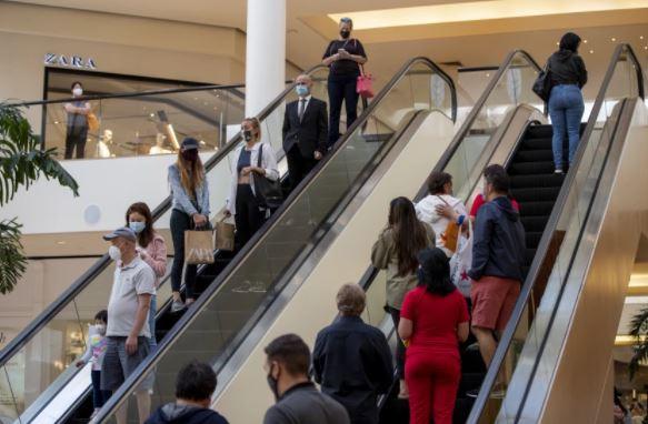 購物者戴口罩在橙縣南海岸購物中心內消費。洛杉磯時報