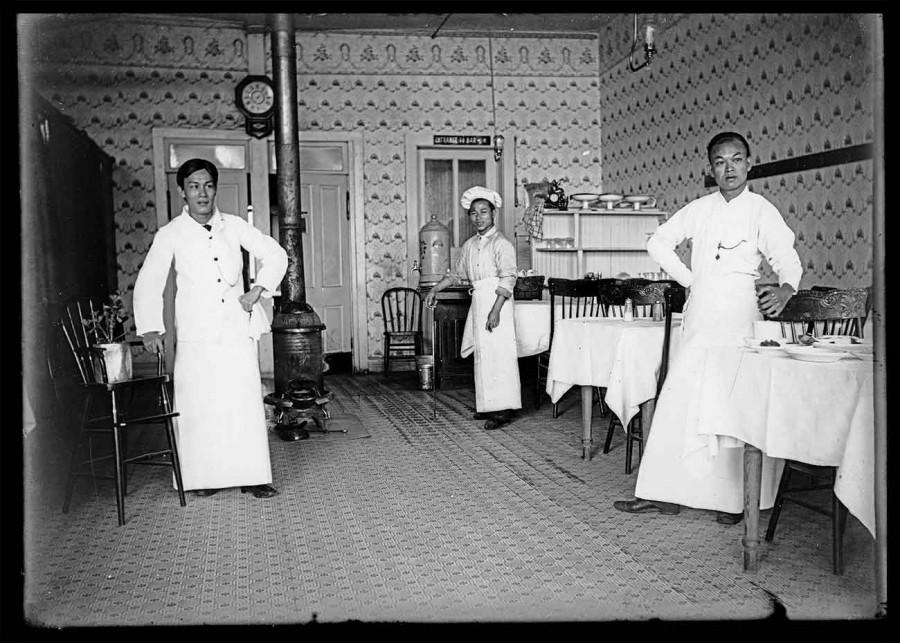 三名華裔男子(廚師和兩個穿著白色長圍裙的服務員)站在一家餐館的桌子中間。杭亭頓圖書館官網