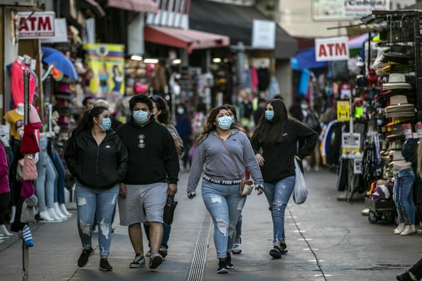 購物者戴著口罩沿著洛杉磯市中心步行。 洛杉磯時報