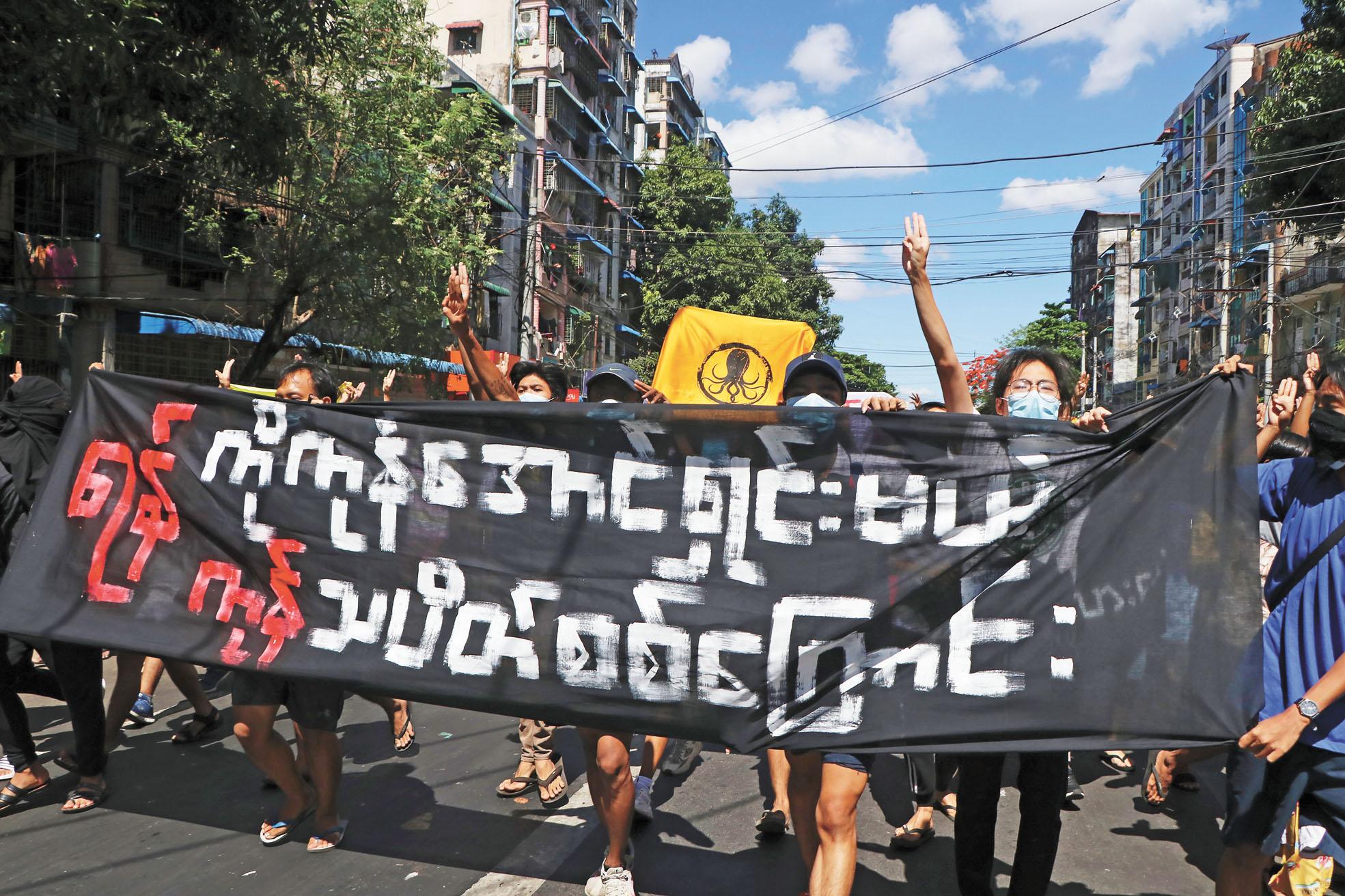 在仰光,示威者拉起橫幅。美聯社
