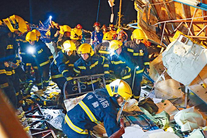 武漢消防人員在龍捲風颳倒的廠房內搜救。