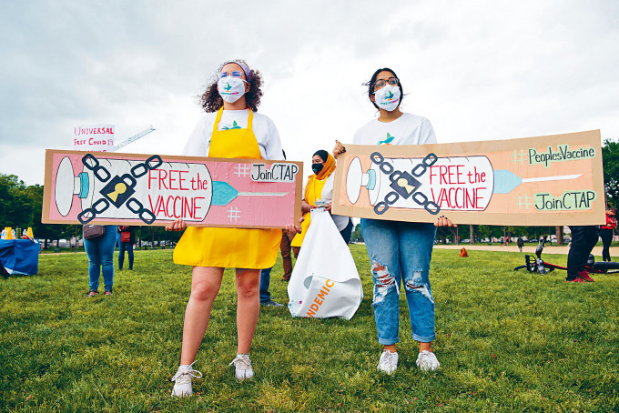 示威者周三展示寫上「解放疫苗」的標語牌,在華盛頓國家廣場呼籲美國開放新冠疫苗專利。