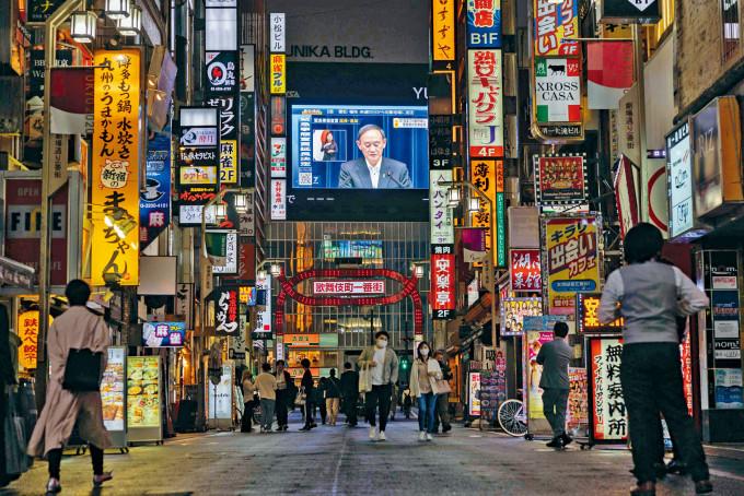 東京冷清的街道上,一個大電視播着菅義偉宣布四都府縣延長緊急事態。