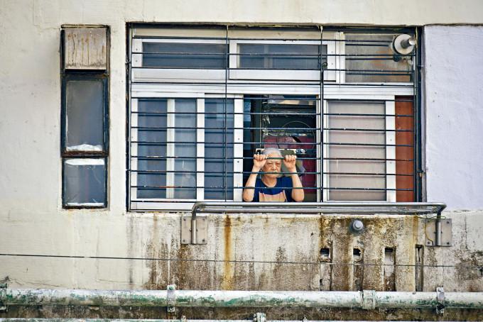 豐興樓進行封區強檢期間,有等候通知的住戶倚窗觀望。