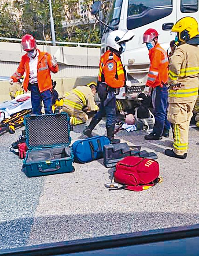 外籍鐵騎士被捲入車底,消防員合力把其救出。