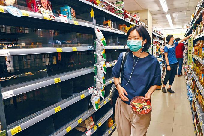 台灣民眾搶囤生活物資,台北一超市貨架被搶空。