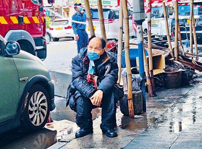 起火單位戶主「教授」坐在街角。
