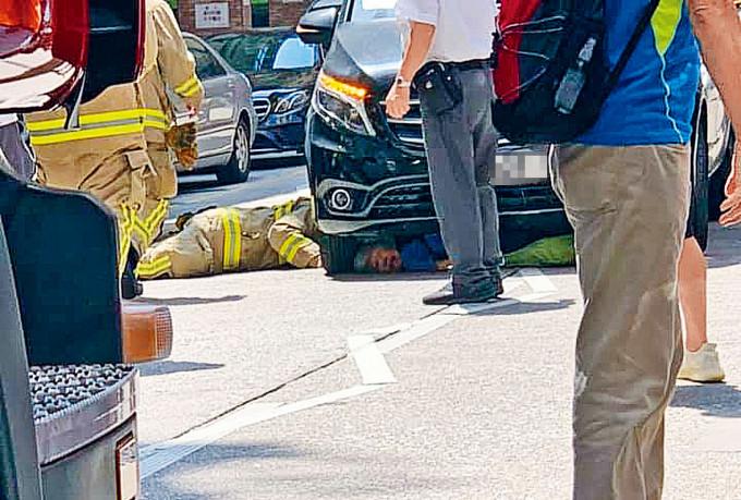 消防員拯救被捲入車底僅露出頭部的老婦。