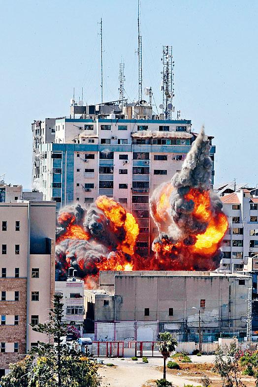加沙市的媒體大樓遭以軍戰機發射導彈摧毀,冒出濃煙。