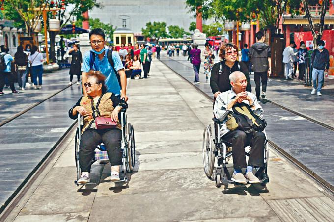 中國人口老化問題加劇。圖為北京兩老人坐着輪椅逛街。