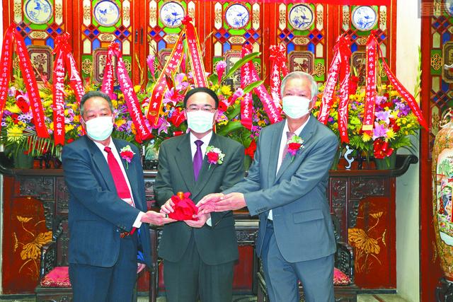 在中領館總領事王東華(中)主持監交下,新任總董朱汝湛(右)從滿任總董司徒仲山(左)手中接過印信,履新上任。馬紅兵攝