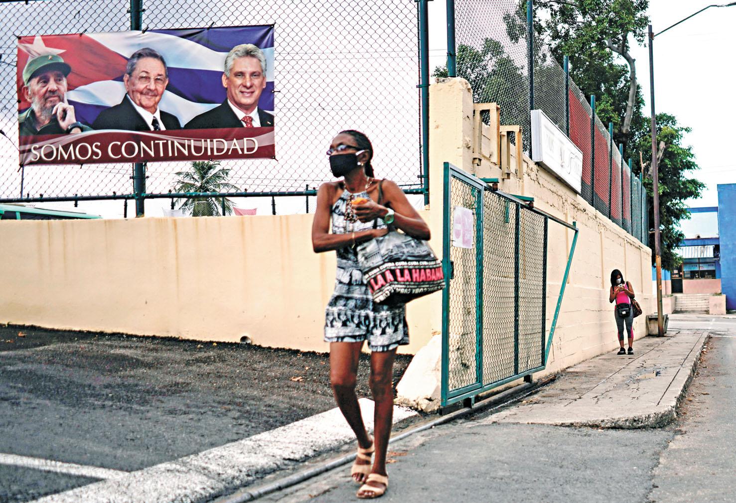 一位古巴婦女在街頭走過,她身後的牆上還貼著卡斯特羅兄弟和卡內爾的畫像。路透社