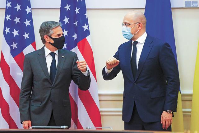 美國國務卿布林肯(左)5月6日在烏克蘭基輔舉行的會談之前,和總理丹尼斯·史密加爾(Denis Shmygal)互相碰臂問候。美聯社