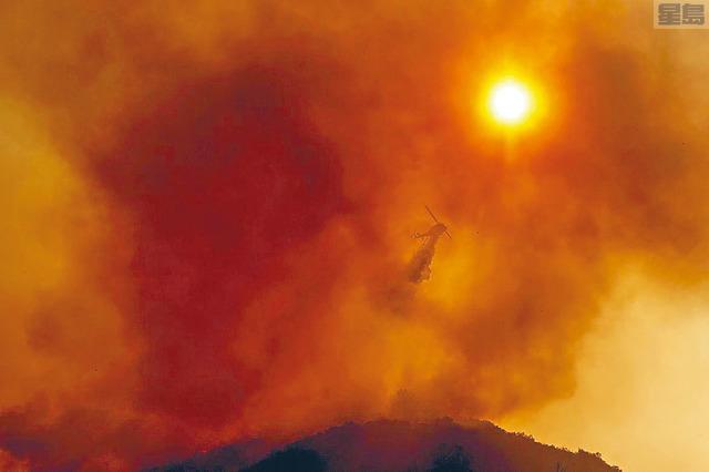 根據國家海洋和大氣管理局的數據,美國不僅變熱,東部和中部地區將更加濕潤,而在西部會更乾燥。圖為去年8月加州薩利納斯的特大山火,直升機在救火。    美聯社