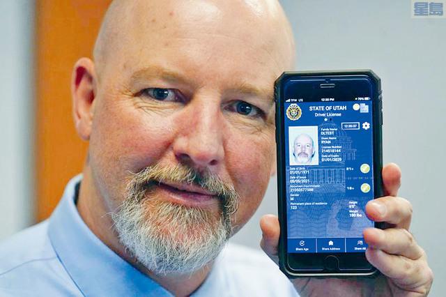 疫情帶動電子錢包愈趨普及,人們也愈來愈依賴手機來證明自己的身分。圖為一名駕駛者展示他的電子駕駛證。美聯社