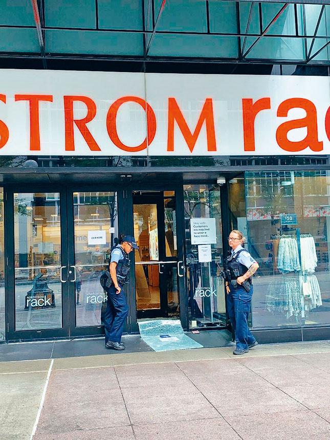 2020年的騷亂中,州街商圈的商家遭受到無情蹂躪,圖為兩名警員無奈的站在連鎖商店「Nordstrom Rack」,被砸碎的玻璃門前把守著。本報檔案照,記者梁敏育攝