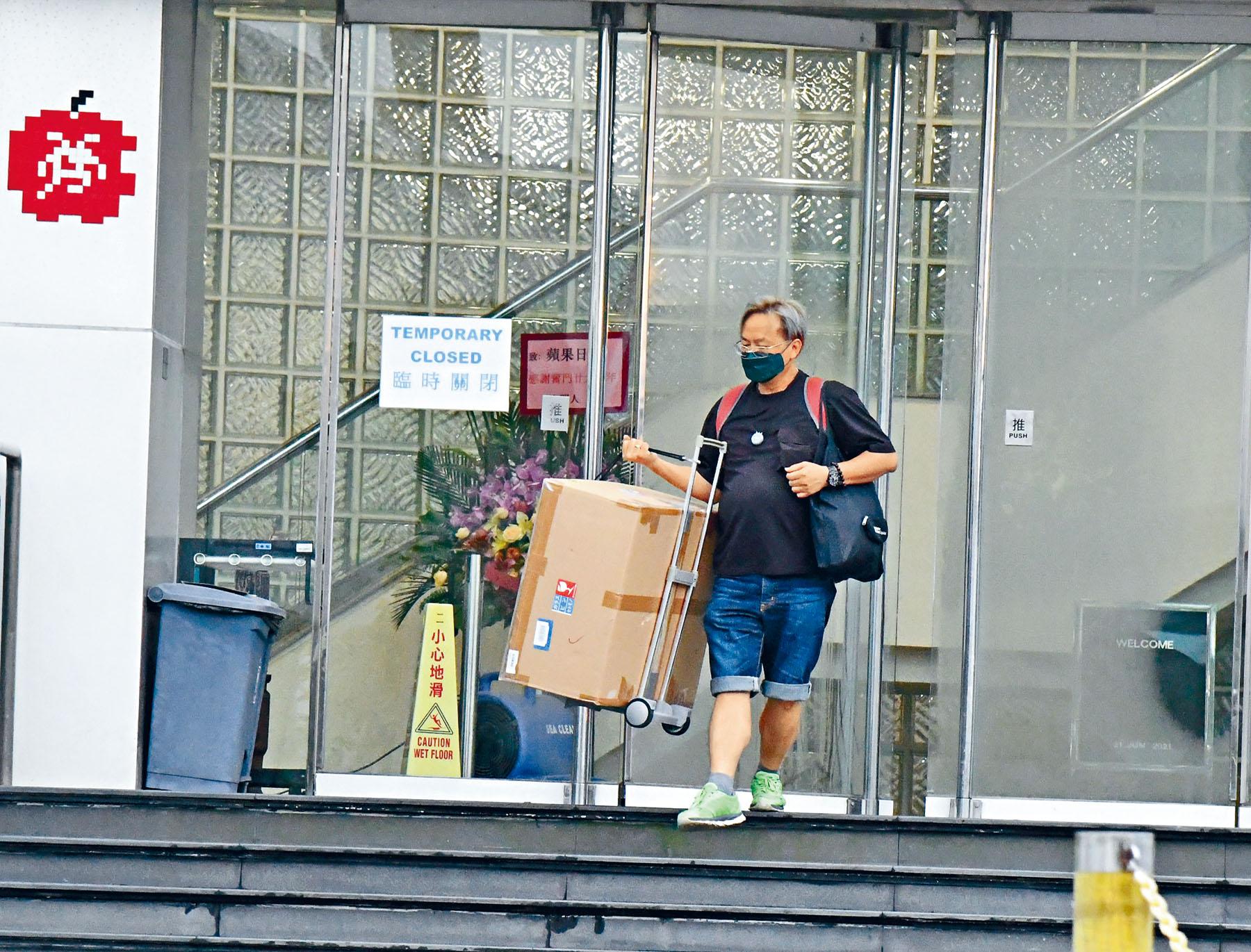 日內停運的消息傳出後,《蘋果日報》大樓出現有下班員工疑拿走私人物品離開。徐裕民攝