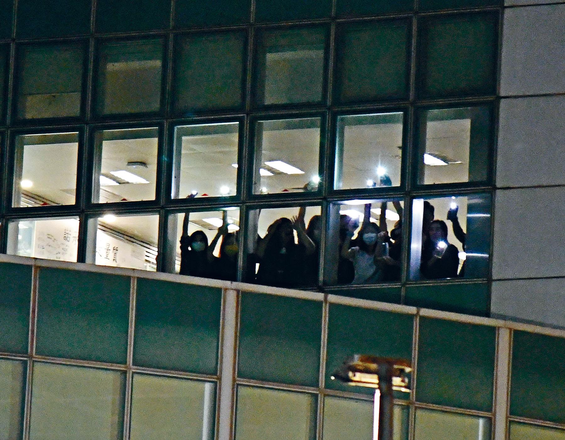 21日晚一批員工隔著玻璃窗,向大樓外採訪記者亮著手機電筒及揮手「道別」。徐裕民攝