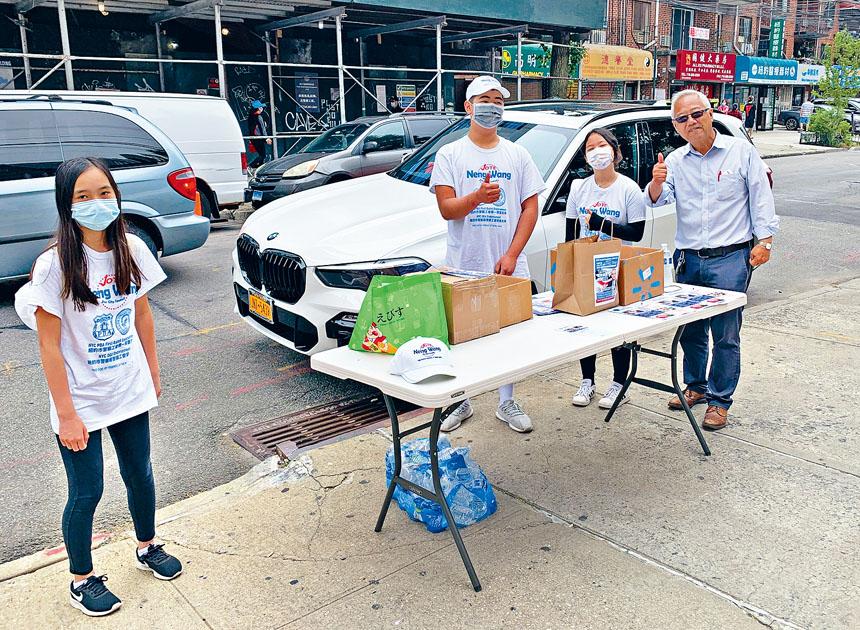 市議員參選人王能(右)在法拉盛41路提前投票站外,與競選團隊義工呼籲選民投票支持。