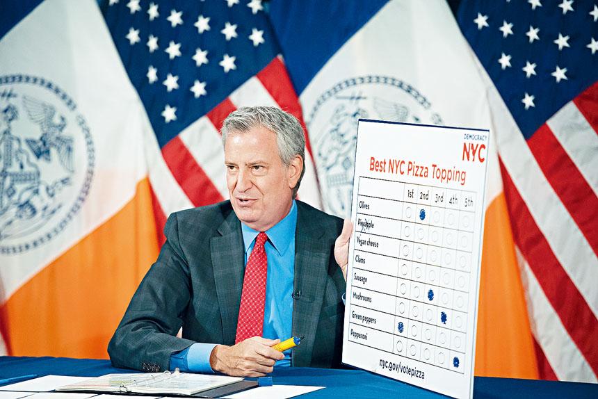 白思豪在記者會上舉起一張「比薩選票」。市長辦公室圖片
