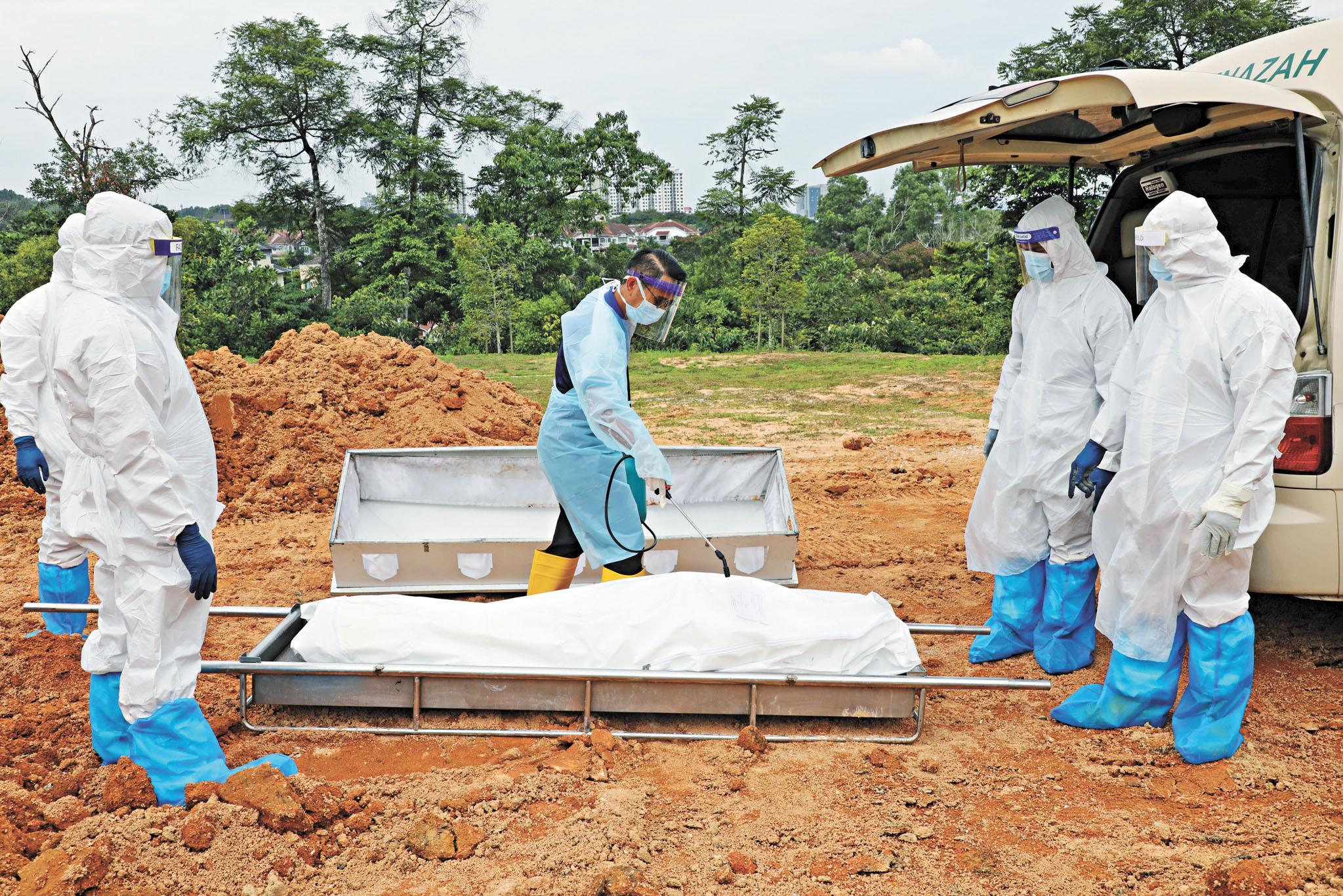 今年迄今全球死於新冠肺炎的人數已超過2020年染疫去世人數的總和,凸顯全球疫情遠未結束。圖為在馬來西亞墓地,工人身穿防護服,準備埋葬新冠死亡患者。路透社