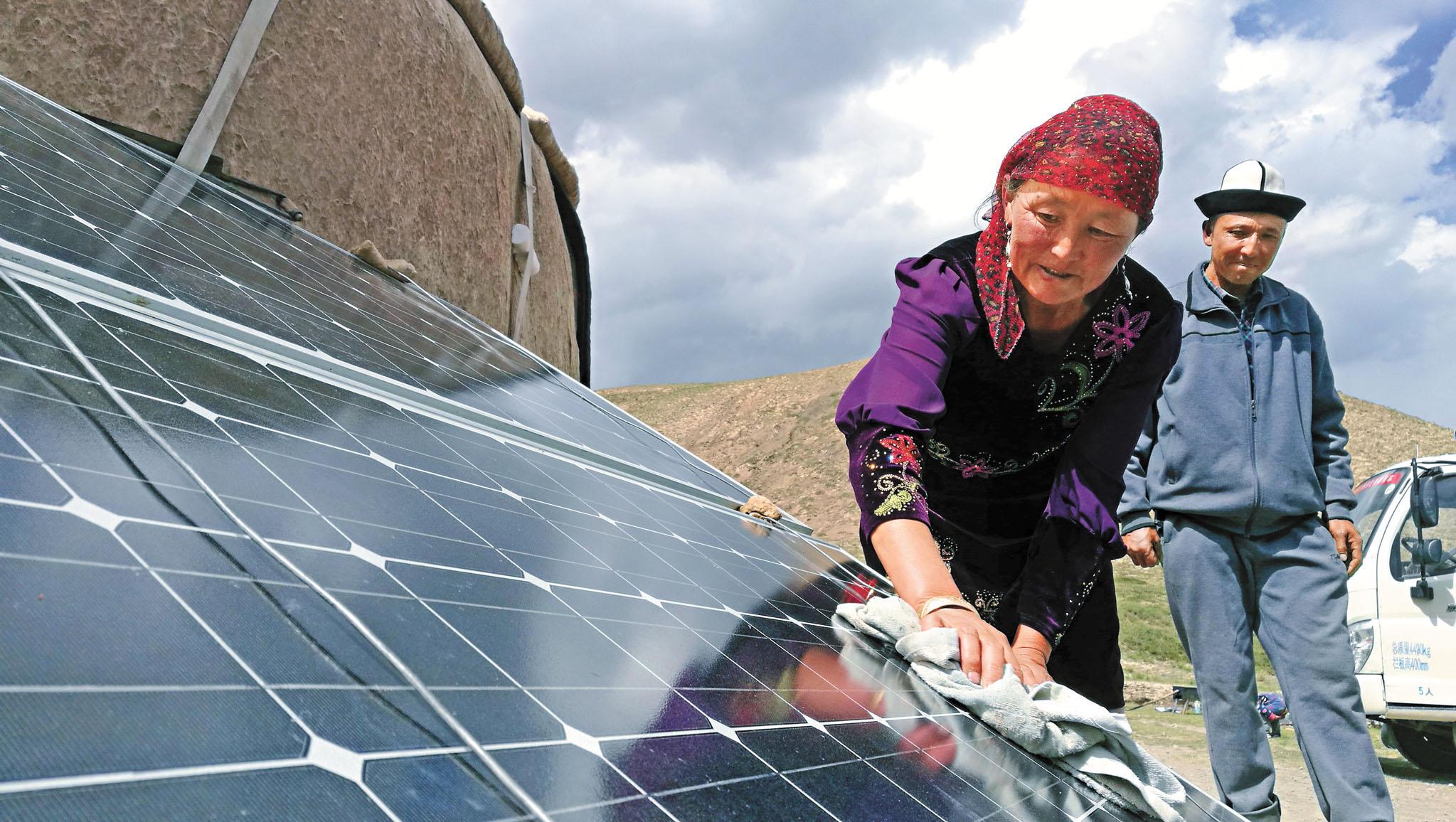 ■多晶矽是製造太陽能板的重要材料。圖為在新疆一牧業點,牧民擦拭光伏板。 資料圖片
