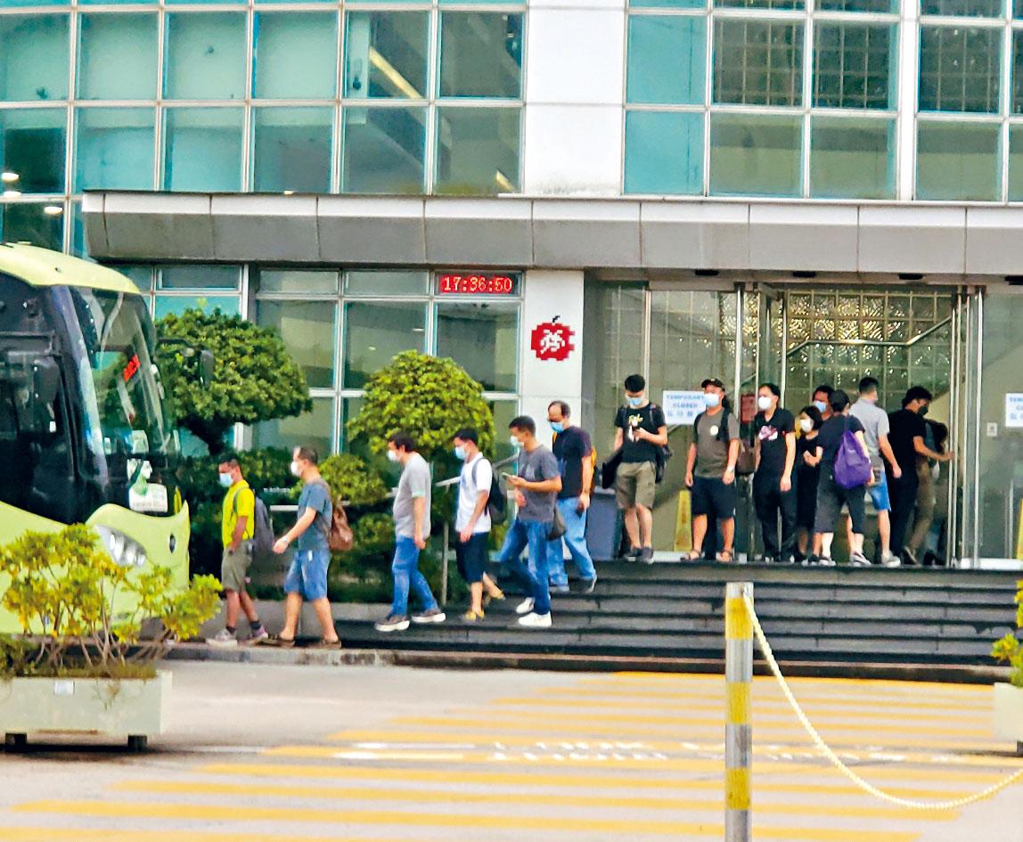 21日大樓門外的公司車,看見仍有不少員工如常上下班。徐裕民攝