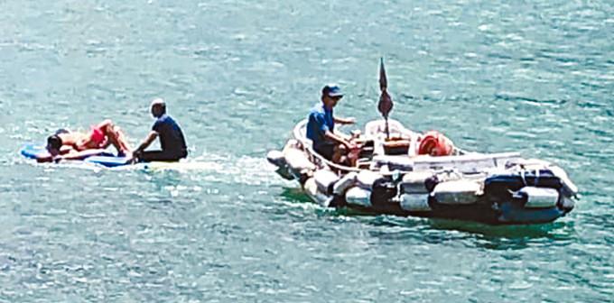 被快艇撞傷的泳客躺臥滑板上,再由救生員駕快艇拖返岸。
