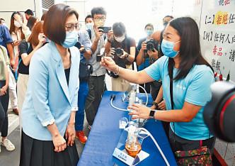 署理總警司吳頴詩(左),觀看供市民體驗仿製毒品氣味的器材。