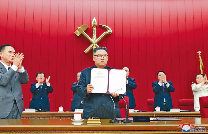金正恩周四出席勞動黨第八屆中央委員會第三次全體會議,展示一份文件。