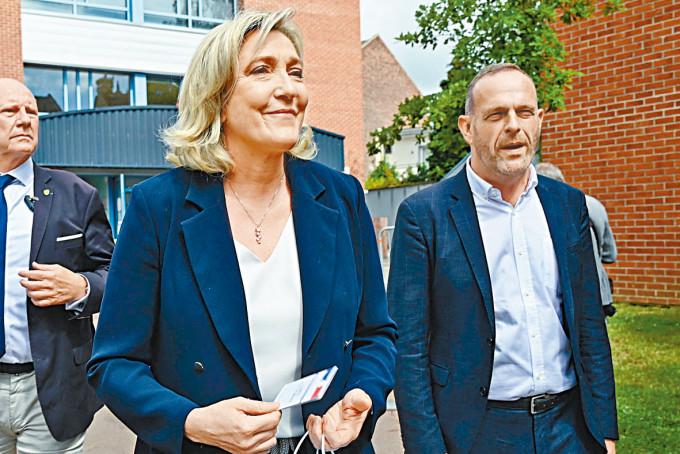 法國極右國民聯盟領袖馬琳勒龐(左)周日離開票站。