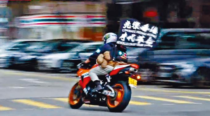 片段顯示被告駕駛插有「光復香港 時代革命」中英標語旗幟的電單車。