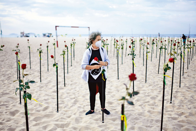 在巴西里約熱內盧的科帕卡巴納海灘上,插滿鮮花悼念該國五十萬名新冠死者。