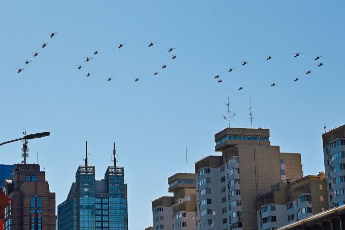直升機排列成「100」字樣通過天安門廣場上空。