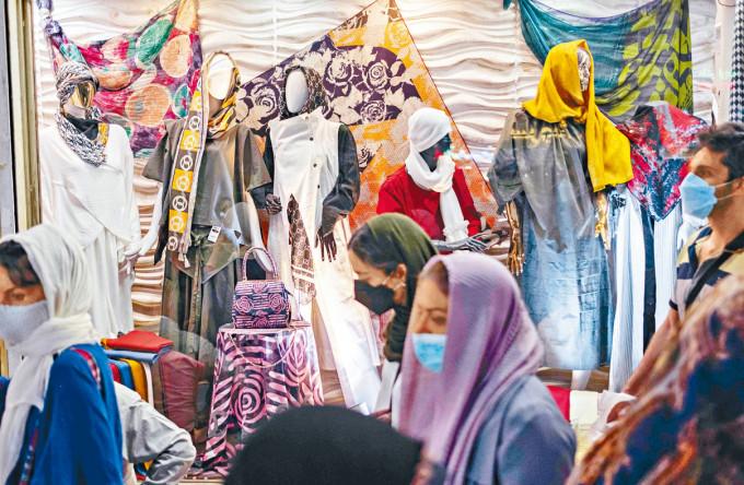 德黑蘭戴口罩的年輕人在逛街。